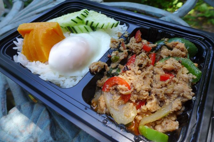 Minced chicken in a black baking tray with rice, a poached egg and pumpkin.