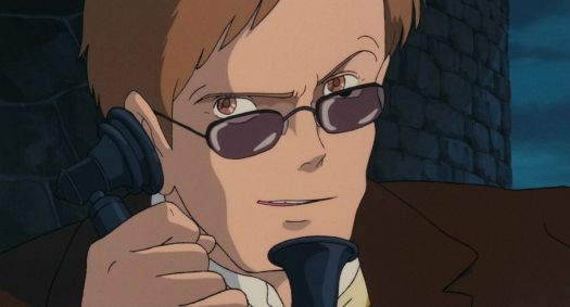A man in brown, with brown eyes, brown hair, and brown glasses, grins as he speaks into an old-timey telephone handset in Castle in the Sky.