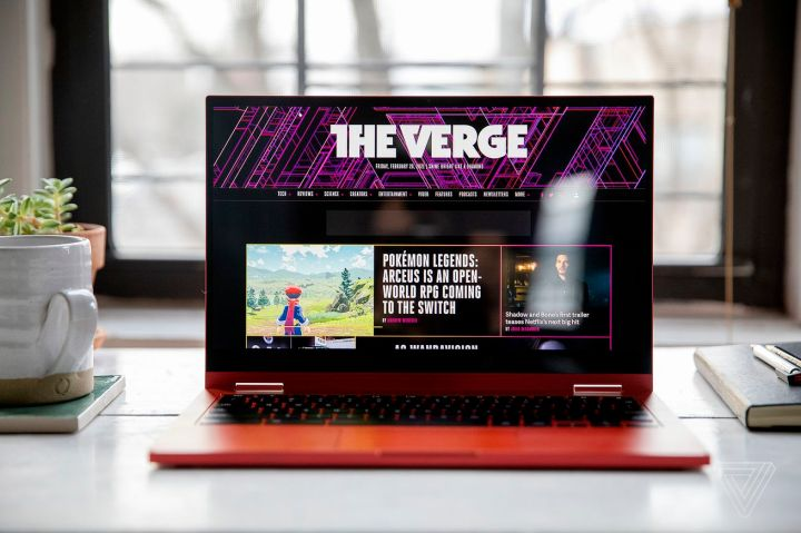 The Samsung Galaxy Chromebook 2 on a desk in front of a window, open with a mug and small plant on its left and some books on its right. The screen displays The Verge homepage.