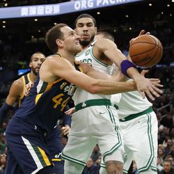 Boston Celtics' Jayson Tatum, front right, fouls Utah Jazz's Bojan Bogdanovic while knocking the ball away during the first quarter of an NBA basketball game Friday, March 6, 2020, in Boston.