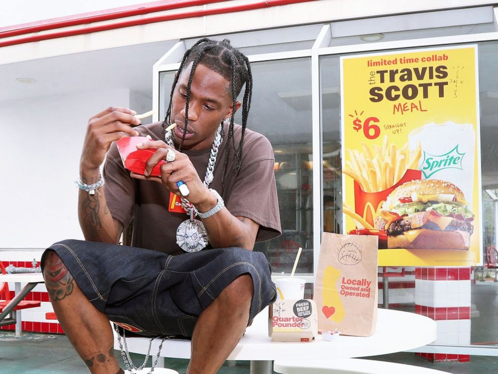 Travis Scott sitting on a table outside McDonald's, advertising his new $6 meal.