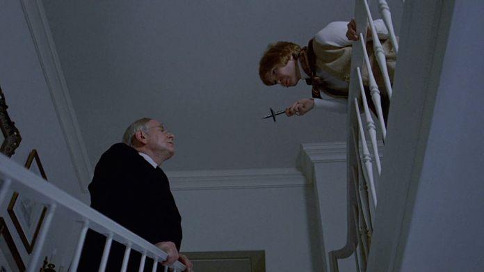 Ellen Burstynbrandishes a crucifix at Rudolf Schündlerin a screenshot fromThe Exorcist