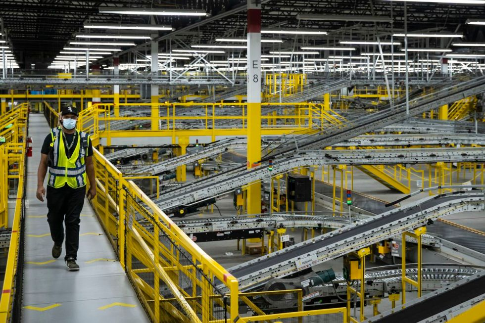 A worker walks across a catwalk at the Amazon MDW7 fulfillment center in Monee. The facility contains about six miles of conveyors.