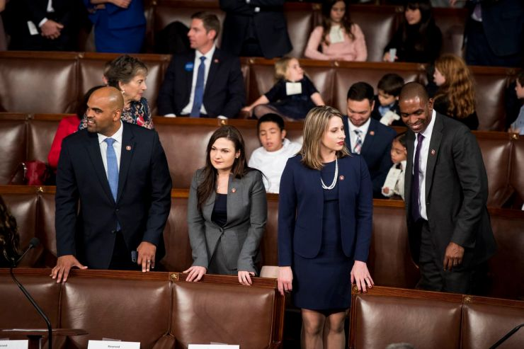 First-term Democratic Representatives Colin Allred (D-TX), Abby Finkenauer (D-IA), Katie Hill (D-TX), and Antonio Delgado (D-NY) stand in the seating area of the House chamber.