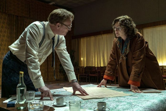 As Valery Legasov and Ulana Khomyuk, Jared Harris and Emily Watson stand over a table covered with documents in Chernobyl