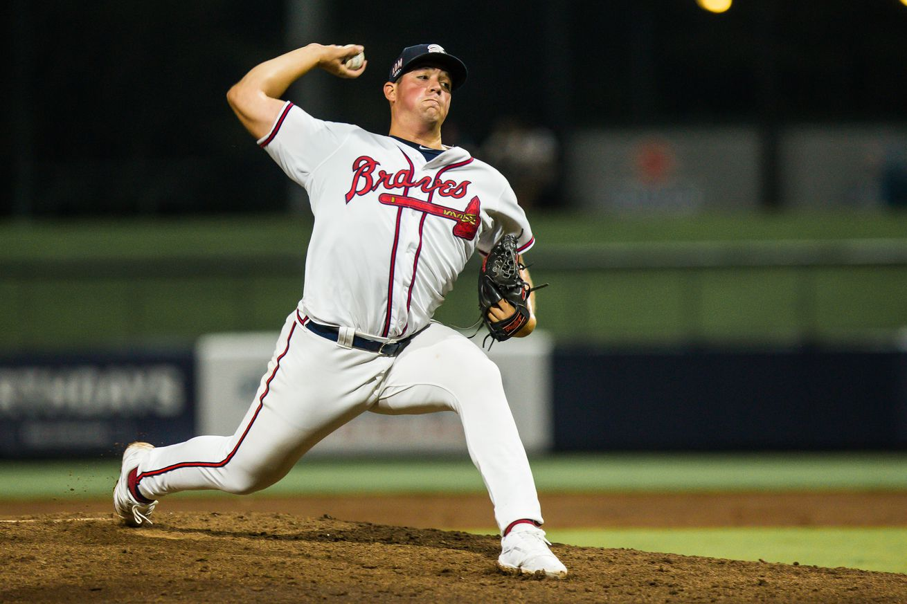 Indigo Diaz, right handed pitcher for the Rome Braves, is in the process of delivering a pitch during a night game