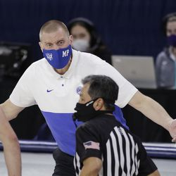 BYU coach Mark Pope chats with an official during the second half of the team's NCAA college basketball game against Gonzaga in Spokane, Wash. On Thursday, Jan.7, 2021.