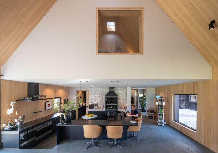 Гостиная с остроконечным деревянным потолком. Кухня и Г-образный остров находятся на первом этаже, а квадратное окно можно увидеть наверху.