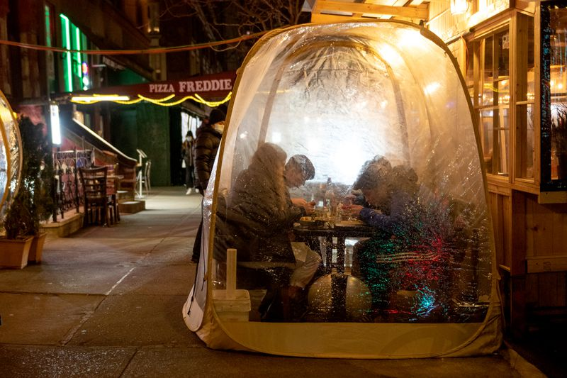 A group of people sitting inside of a plastic bubble on the sidewalk at night