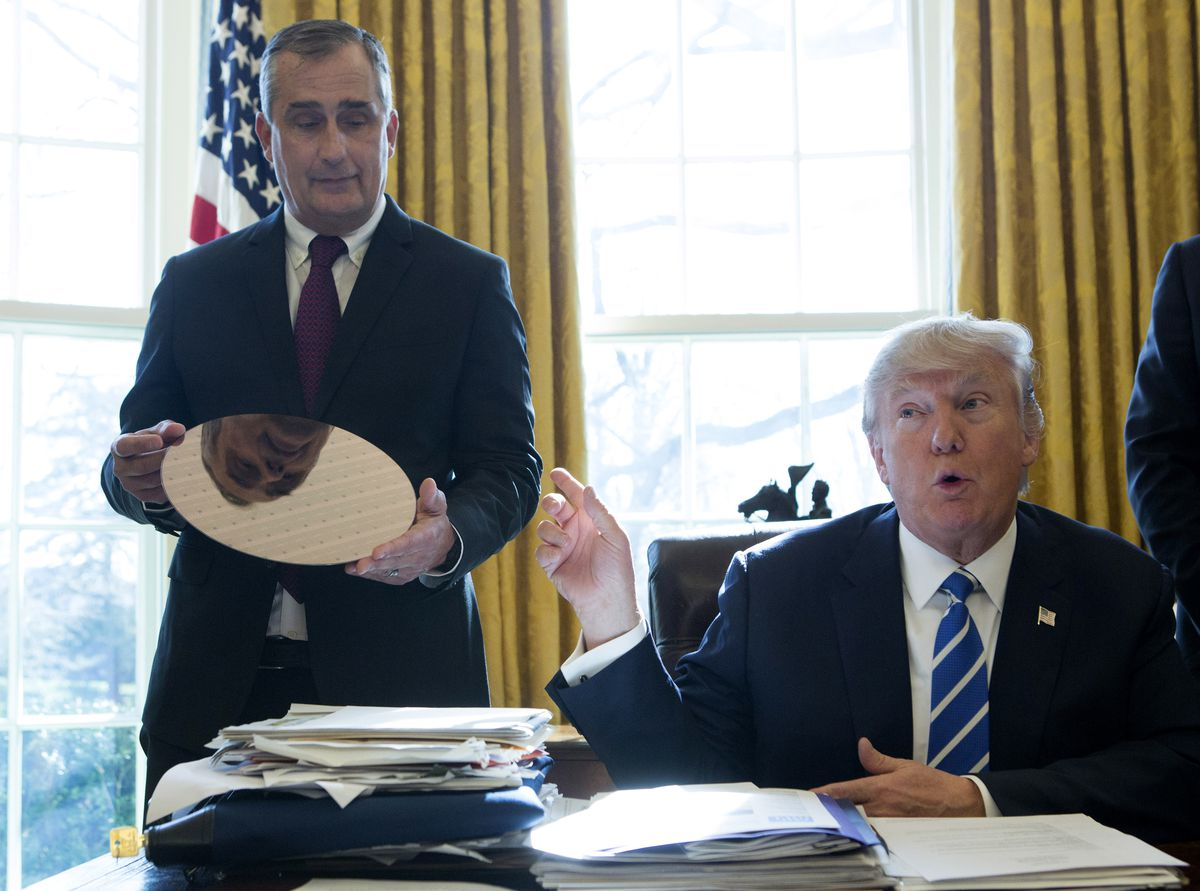 President Trump sitting as his desk in the Oval Office with Intel CEO Brian Krzanich standing behind him holding a reflective circle of silicon.