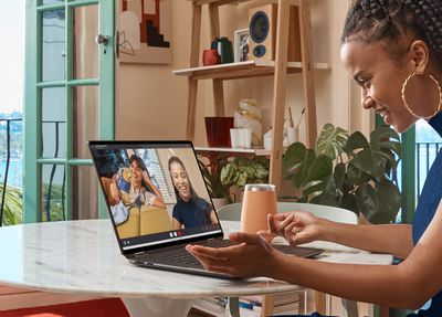 A user participates in a video call on the HP Spectre x360 16. The laptop is seen from the side and sits on a marble table. A hydroflask is to its right, as is a shelf populated with two potted plants, a stack of books, a number of glass cups and jars, a pencil pot, and a speaker.