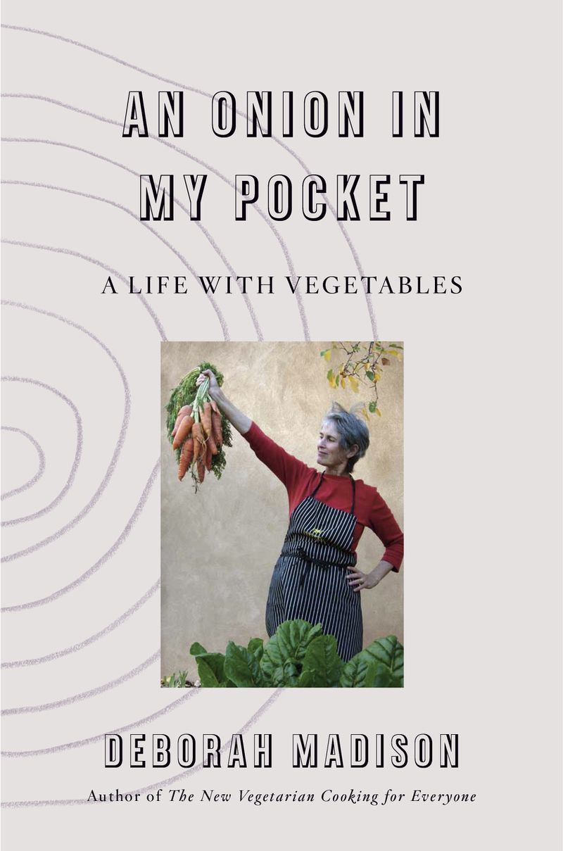 A woman holds up a bushel of carrots on the book cover for An Onion in My Pocket