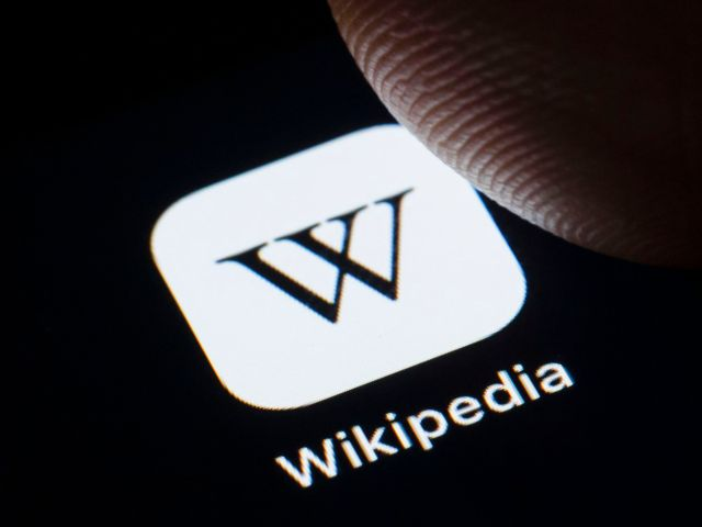 Wikipedia's logo displayed on a smartphone with a person's finger hovering over it.