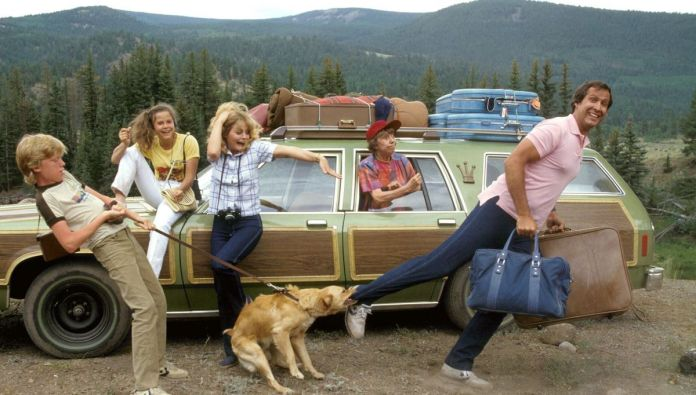 The Vacation cast poses in front of their ugly green station wagon, with Chevy Chase holding up a couple of suitcases as the family dog they're transporting pulls on his pant leg with its teeth.