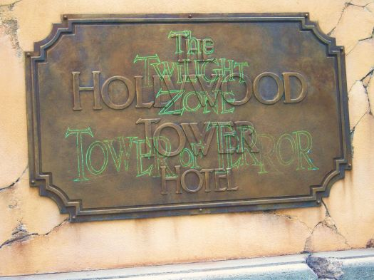 """a brass plaque that says """"The Hollywood Tower Hotel"""" with the words """"The Twilight Zone Tower of Terror"""" projected onto it in green text"""