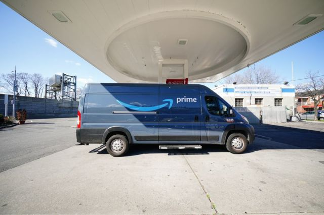 An Amazon Prime delivery van parked at a gas station.