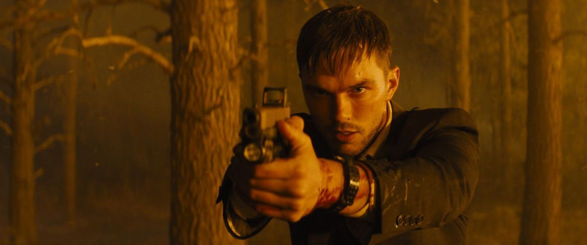 An agitated, bloodied Nicholas Hoult points a gun offscreen in Those Who Wish Me Dead