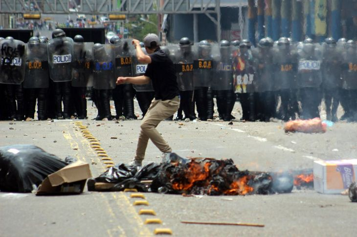 A student demonstrates in front of a line of riot police during a protest against Venezuelan President Nicolás Maduro's government in San Cristobal, Venezuela, on February 12, 2015. George CASTELLANO/AFP/Getty Images
