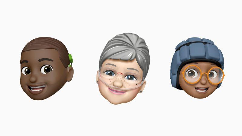 Tre Memoji sorridenti, che mostrano uno con un impianto cocleare a sinistra, uno con tubi di ossigeno nasali al centro e uno con un elmetto morbido a destra.