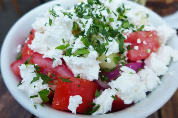 A bowl of tomatoes, cucumbers and fluffy white ricotta.