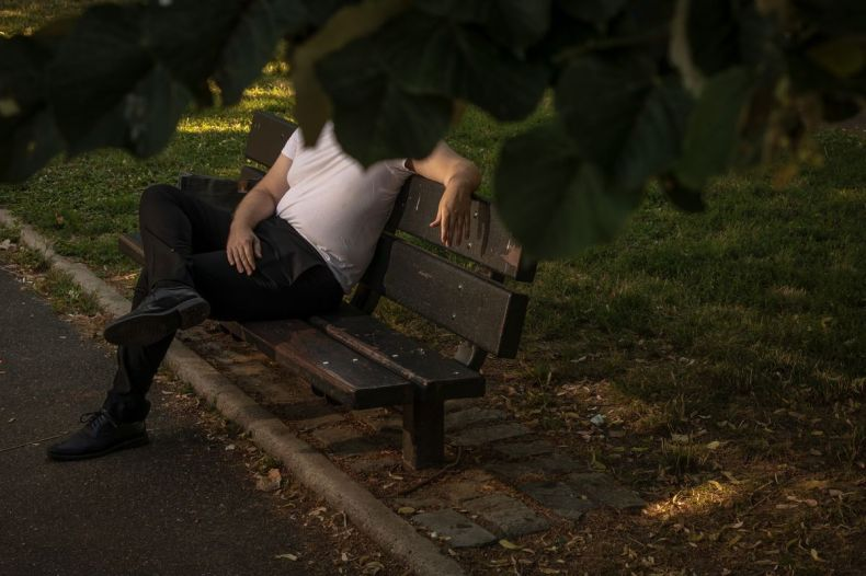 A man sits in a park with his face obscured by leaves
