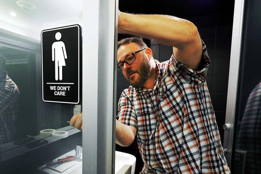El gerente del museo Jeff Bell coloca carteles de género neutro en los baños públicos del 21C Museum Hotel en Durham, Carolina del Norte, el 10 de mayo de 2016.  Sara D. Davis / Getty Images