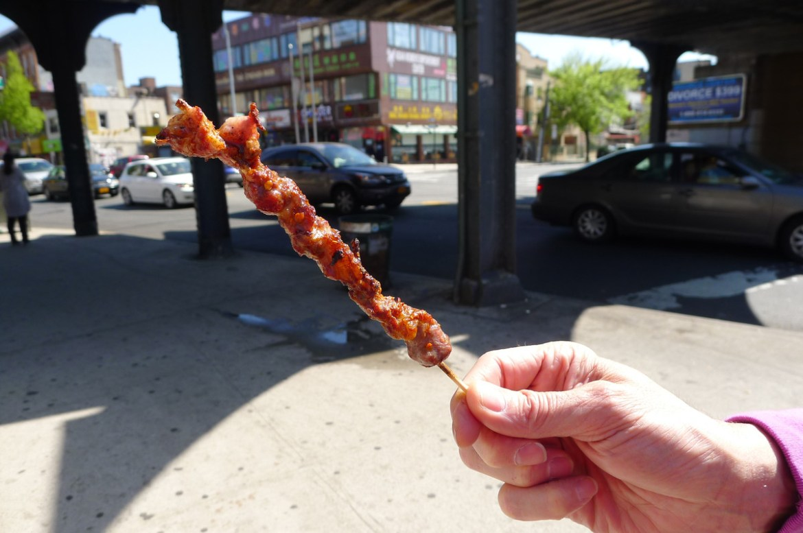 A hand holds up a grilled meat skewer outside