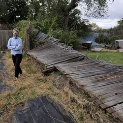 Haylee Chaffee walks by a fence that fell down in her backyard during a windstorm in Salt Lake City on Tuesday, Sept. 8, 2020.