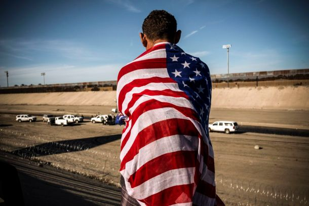 A Central American migrant wrapped in a US flag looks at the almost dry riverbed of the Tijuana River near the El Chaparral border crossing near US-Mexico border in Tijuana, Baja California State, Mexico, on November 25, 2018.