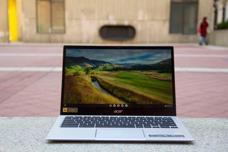 L'Acer Chromebook Spin 513 si trova su una panchina di pietra, aperto.  Lo schermo mostra una scena pastorale.