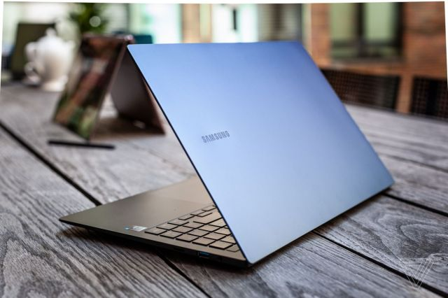 The Samsung Galaxy Book Pro half open, angled away from the camera slightly to the right on a picnic table.