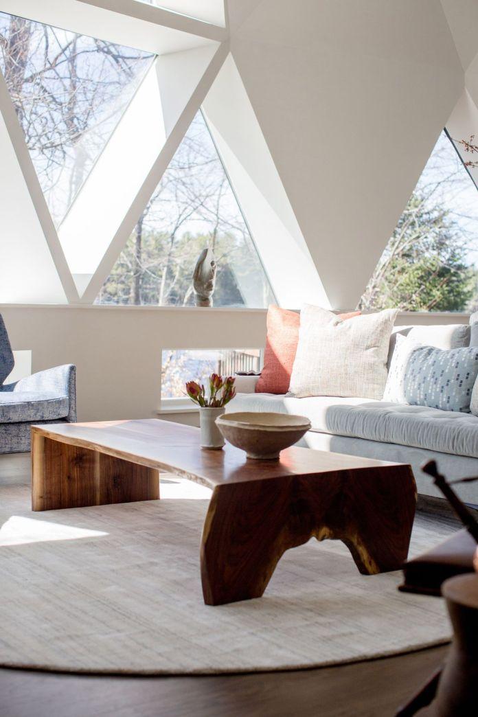 Гостиная с серым диваном и деревянным журнальным столиком перед треугольными окнами.