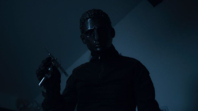 A man in a black metal mask holds a syringe in 2021's Held