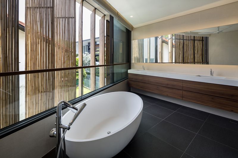 Bathroom with windows clad in bamboo screens.