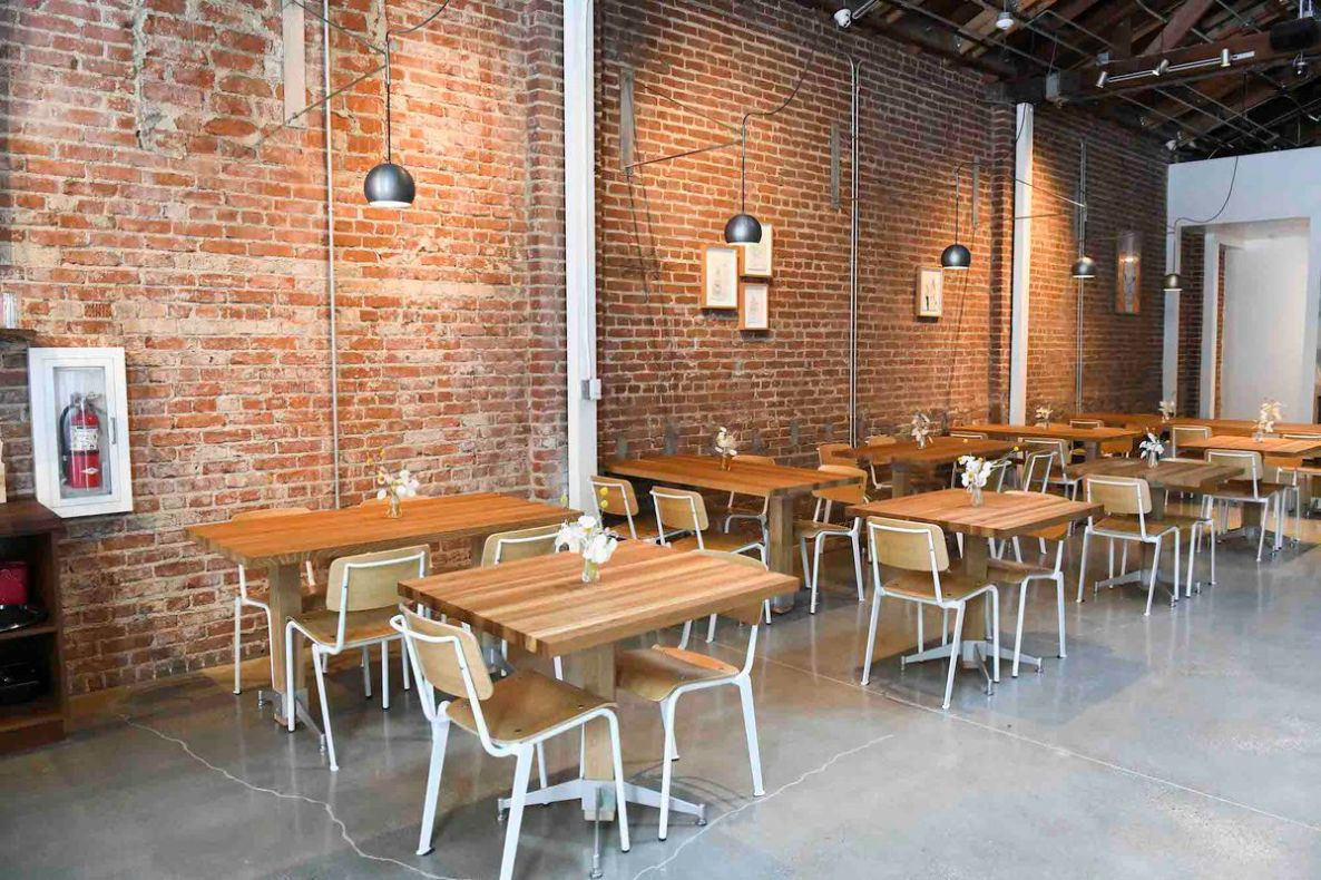 Brick walls and hanging lights over wooden tables.