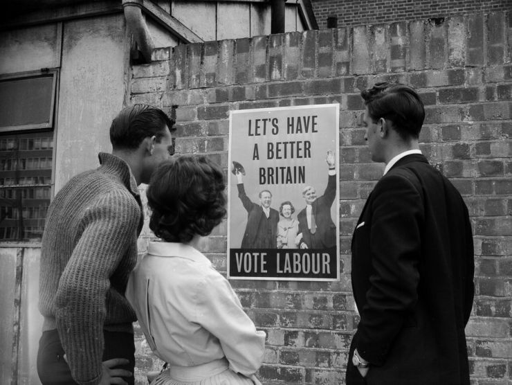 "Onlookers view a political poster issued by the British Labour Party that reads ""Let's have a better Britain. Vote Labour!"" on September 24, 1959."