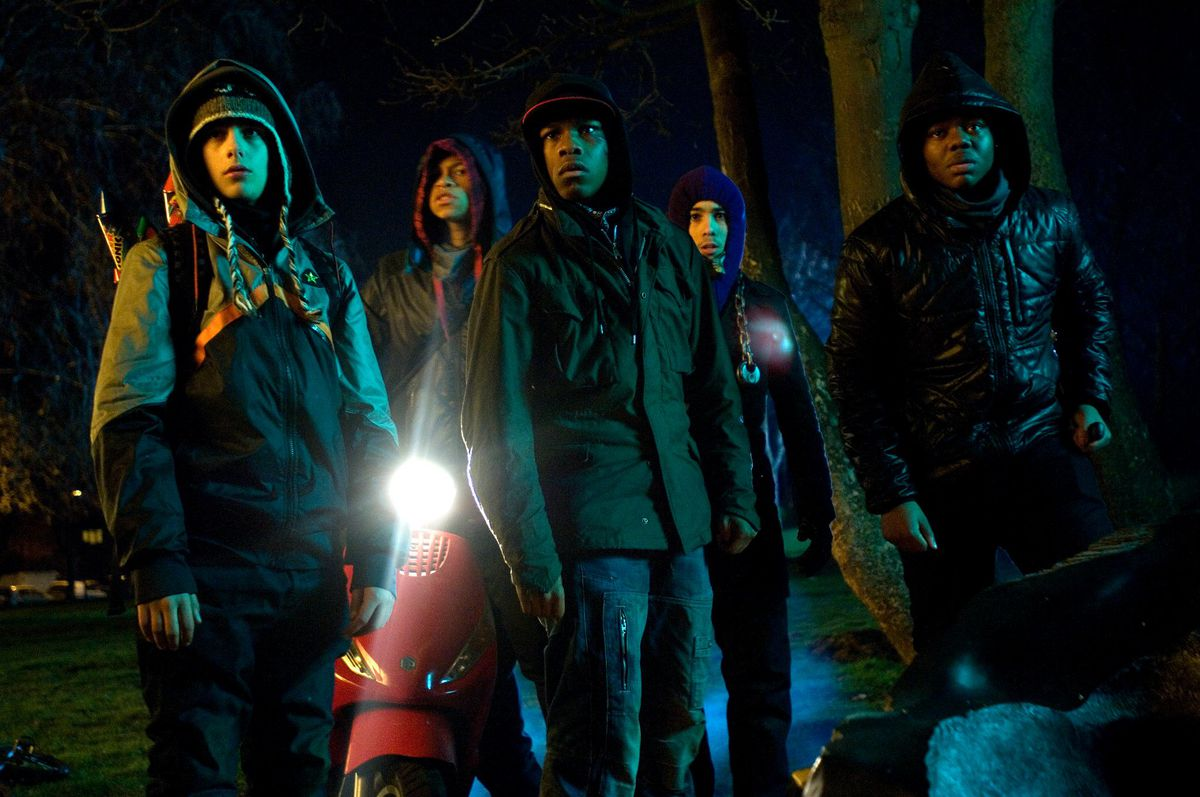 The cast of Attack the Block stand in front of a motor scooter