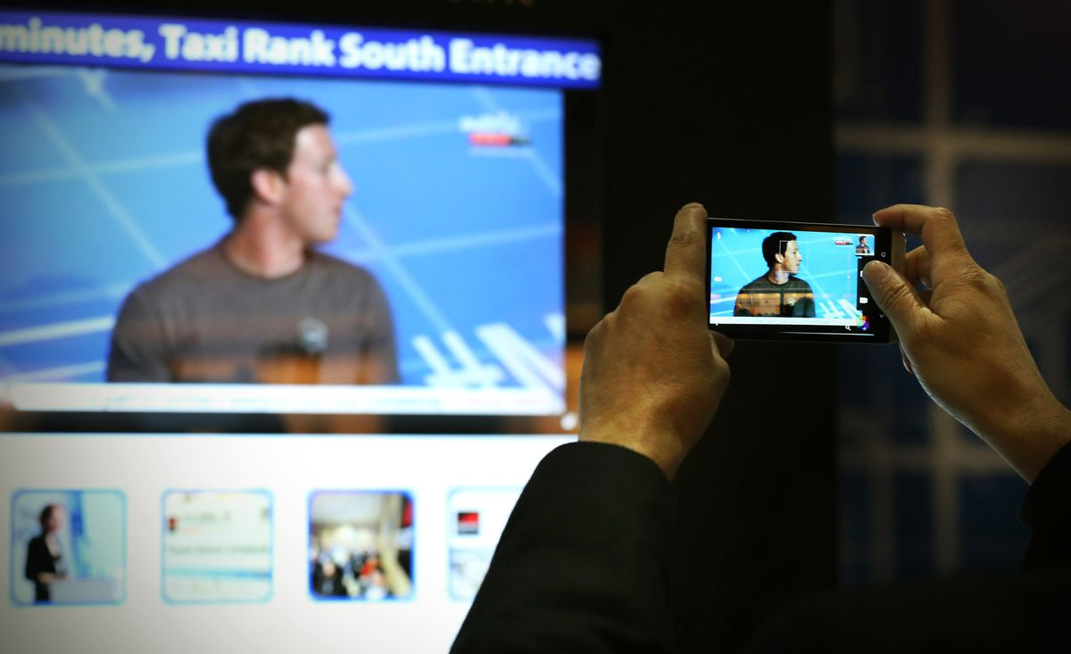 A bystander takes a photo of Mark Zuckerberg on their mobile phone.
