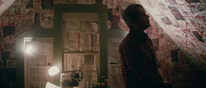 A man stars at a wall covered in newspaper and red string