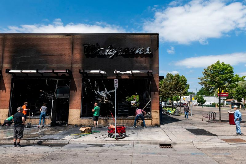 People begin cleaning up the sidewalks outside a Walgreens store in Minneapolis on May 30.