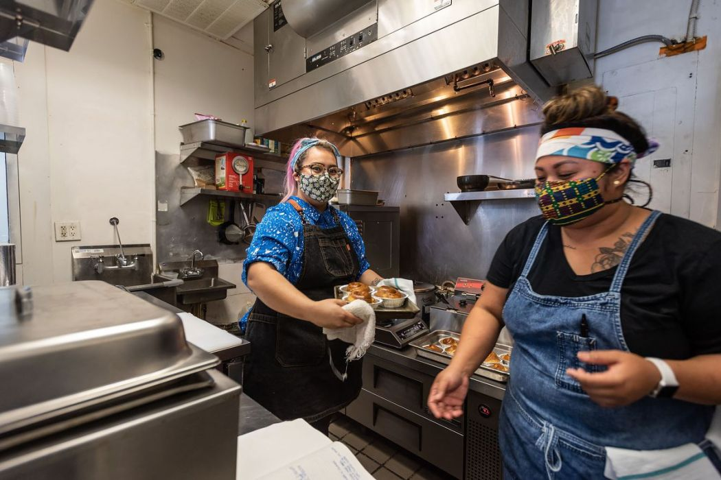 Workers wearing masks handle food inside of a kitchen.