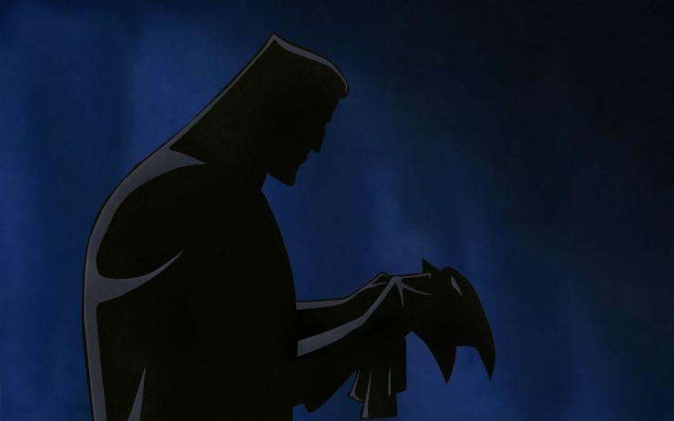 un hombre mira una máscara en batman: máscara del fantasma