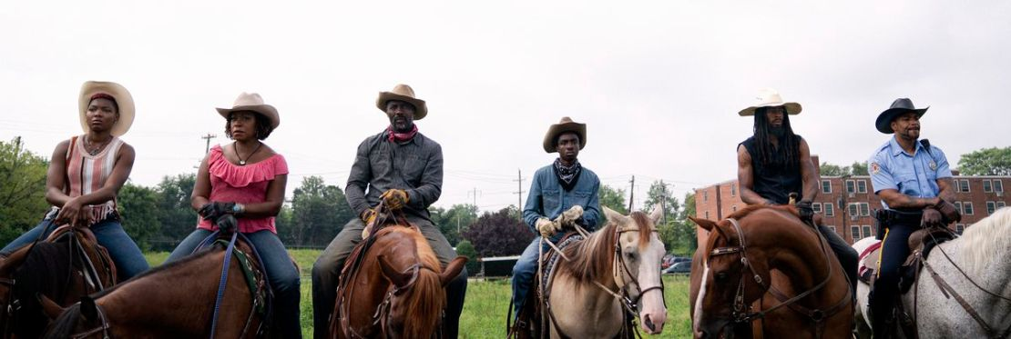 A row of modern-day Black cowboys on horses in Concrete Cowboy, including Ivannah Mercedes, Lorraine Toussaint, Idris Elba, and Caleb McLaughlin