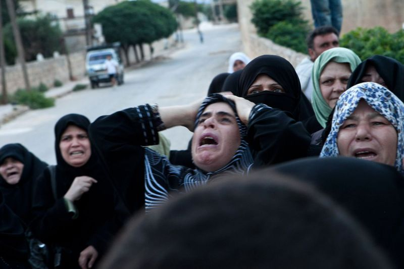 Syrian relatives mourn during the funeral of Mohammed Ahmed Rahim in Idlib province on June 22, 2012.