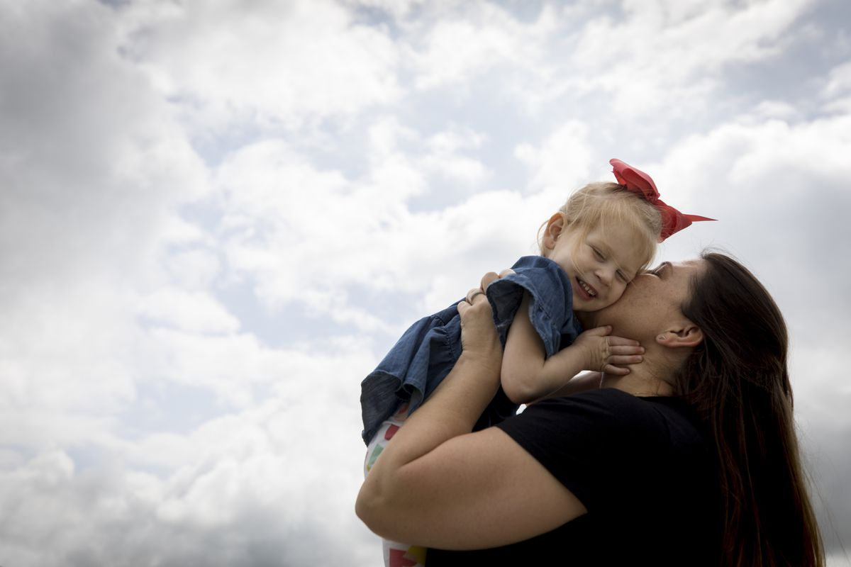 Lindsay Clark kisses her daughter Lily outside their home in Aledo, Texas.