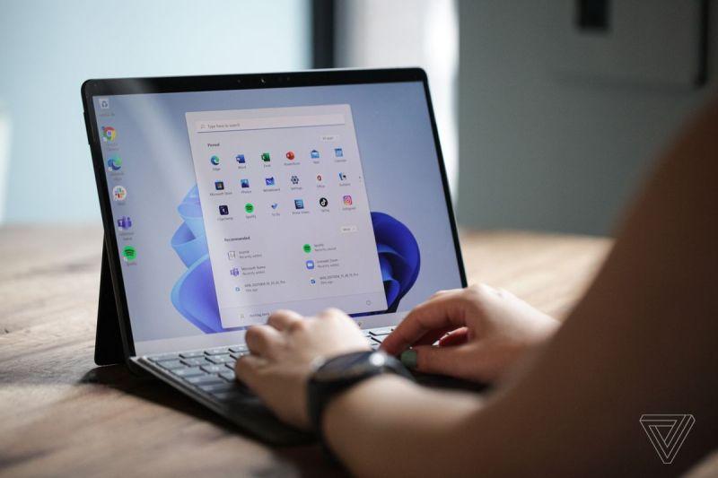Un utente digita su Surface Pro 8 da dietro.  Lo schermo mostra il menu di avvio di Windows 11 su uno sfondo bianco e blu.