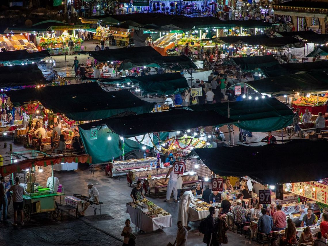 From a nearby rooftop, the Jemma el Fna market at night, with rows of stalls lit by harsh lights, vendors and customers mingling, and numbers hanging from awnings above each vendor.