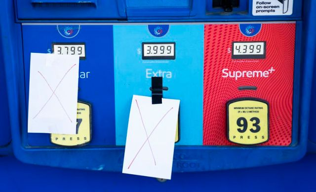 A gas pump with two paper X's taped to the front, indicating that they are out of gas.