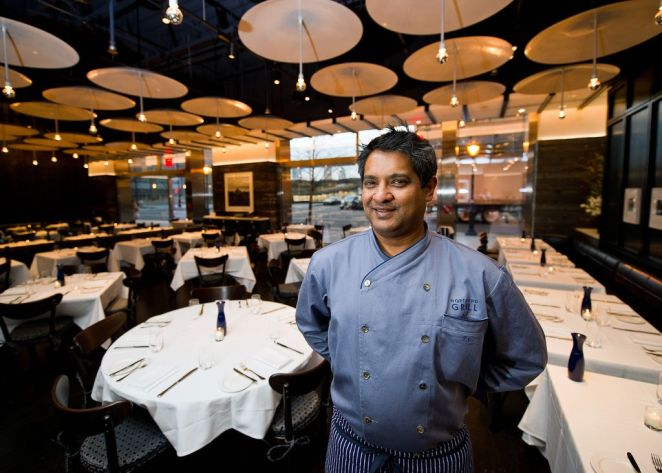 Floyd Cardoz, wearing a blue shirt, stands in an empty dining room.