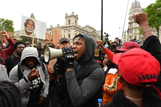 John Boyega speaks through a megaphone to a large crowd of protesters